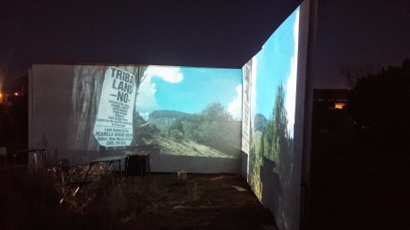 "Title: See Ka Dimensions: 20'L x 16'H Materials/ Techniques: On site installation. Found high school desks. Constructed walls. Video Projections on all walls at night Site: Santa Fe NM About: ( ""listen"" Tiwa origin: Picuris Pueblo NM ) This work is about the connection between language, land and their relationship to one's identity within contextual space. There is a way that the Installation acts as catalyst of time from sunrise to sunset, as if from generation to generation and the relationship of time and identity Vimeo: https://vimeo.com/123798818"